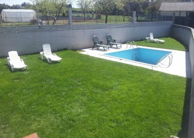 Zona verde con piscina y tumbonas.
